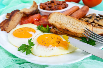 Traditional English breakfast: bacon, mushrooms, eggs, tomatoes, sausages, beans, toast on a white plate on a bright wooden background.  England classic cuisine. Close up