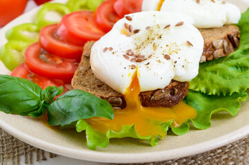 Sandwich with egg poached, lettuce, black bread with seeds, tomatoes, sweet pepper on a plate on a white wooden table. Close up
