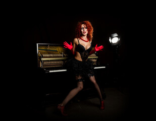 Sexy girl looks like a doll with curly redhead standing next to a piano, on a dark background. Fashion style