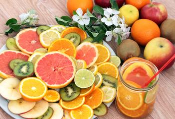 банка с фруктовой водой для очищения организма из цитрусовых на фоне фруктов и веточки цветущей яблони