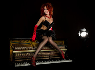 Sexy girl looks like a doll with curly redhead sits on a piano, on a gray background. Fashion style