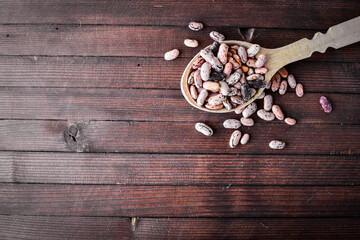 kidney beans. Wooden spoon. On Wooden background. Top view.
