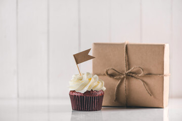 Fathers day concept. Delicious creative cupcake and gift box on table.