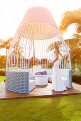 Beautiful blonde bride in white wedding dress and the groom in a white gazebo at the hotel. Tropical skies and palm trees in the background. Summer vacation concept.