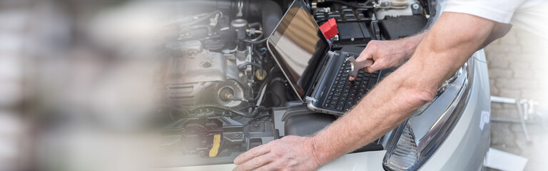Mechanic using laptop for checking car engine