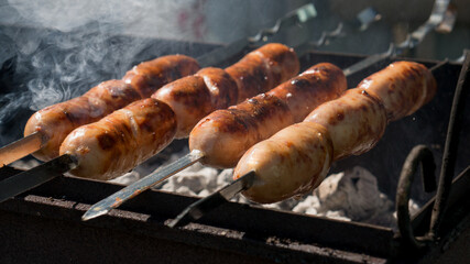 Delicious, juicy sausages roasted on a spit over an open flame . A horizontal frame.