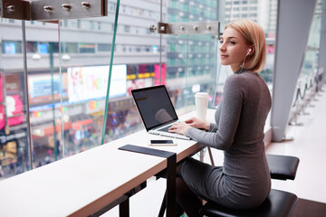 Attractive young hipster girl work break in coffee shop enjoying favorite song from playlist via smartphone and earphones,talented female journalist typing text of article listening to radio broadcast