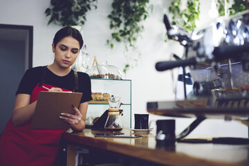 Concentrated professional administrative manager of coffee shop making revisions after working day using documentation and accounting of incomes from service and sale and cost making report