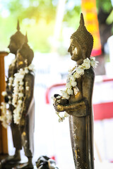 Buddha statue with Jasmine bunch at a Thai Buddhist temple.