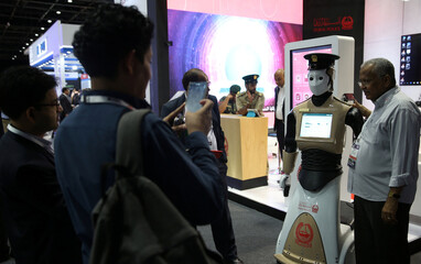Visitor has a picture taken wtih an operational robot policeman at the opening of the 4th Gulf Information Security Expo and Conference (GISEC) in Dubai