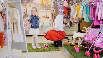 Shopping for kids. Mom and daughter admire her attire in front of the mirror