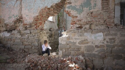 The boy hides and cries, in a ruined building after the war, lost, fear, loneliness, threat, loss