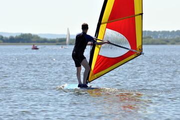 Ein Windsurfer gleitet auf dem See