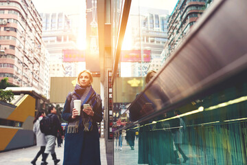 Attractive young blonde female walking down city street of Chinese megalopolis with cup of coffee holding modern smart phone using navigator and fast 4G internet in roaming fascinated by buildings