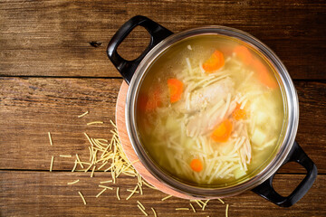 Homemade chicken soup with noodles and vegetables in metal pan on wooden table.