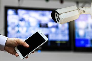CCTV security camera monitor in office building and a businessman hand holding a smart phone.