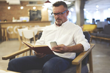 Handsome male dressed in trendy clothes fond of reading enjoying leisure spending with book taking photos of favorite paragraph to share with followers in social networks using phone connected to wifi