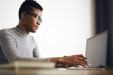 Portrait of intelligent female teacher in glasses reading reports of talented students correcting mistakes and putting marks sending feedbacks on email box via laptop computer connected to wifi