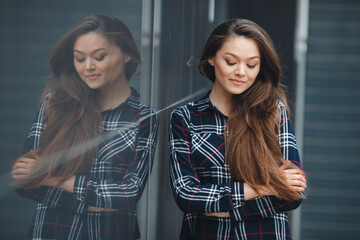 A young leader, a beautiful modern woman, a brunette with long straight hair and brown eyes,is dressed in a plaid shirt, posing standing outdoors standing near the mirror wall of the office