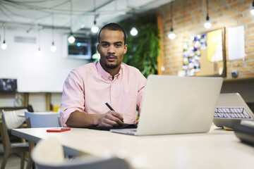 Portrait of concentrated male entrepreneur working with financial documentation and statistic reports in online database counting sum of costs and income of his business startup using laptop and wifi