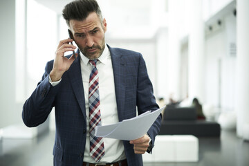Confident busy executive manager of successful business enterprise having phone conversation with secretary assistant arranging conference meeting with departure leader to discuss financial report