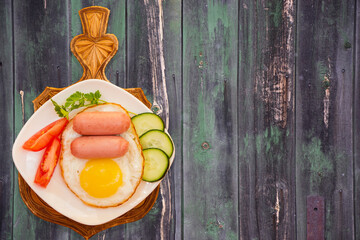 Breakfast of scrambled eggs and mini sausages with vegetables on white plate on gray wooden table vintage top view