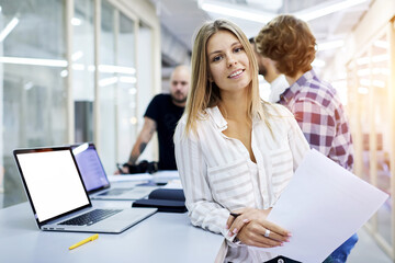 Portrait of attractive smiling female business coach preparing for lesson with international student standing in classroom near  modern laptop computer with mock up screen connected to internet