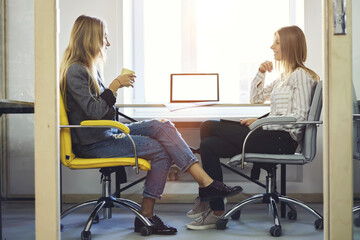 Female colleagues enjoying friendly conversation with cup of coffee during work break in coworking office sitting near modern laptop computer with mock up screen connected to wireless fast 4G network