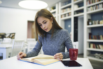 Young attractive female student dressed in trendy clothes sitting at table in modern university library while reading book preparing for literature lesson using technology and wireless connection