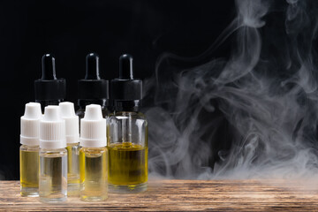 Set of smoking liquids in glass jars on a background of smoke