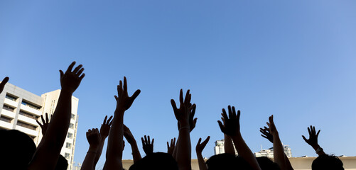 community initiative or volunteering concept, hands of group of people in the blue sky, silhouette