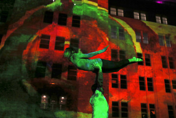 A yoga group named AcroJam Sydney practice poses in front of the illuminated facade of the Museum of Contemporary Art during the Vivid Sydney festival of light and sound in Sydney