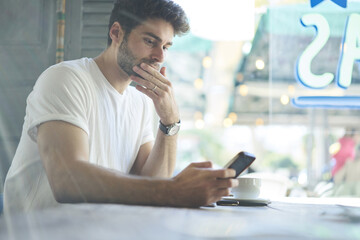 Pensive skilled hipster guy searching information and chatting with friends about meeting in social networks via smartphone using 5G internet connection sitting with cup of coffee in urban coffee shop