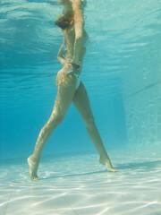 corps de femme sous l'eau qui fait de l'aquagym