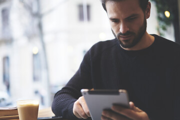 Serious freelancer dressed in casual outfit focus on reading news and looking on digital tablet while sitting in cozy urban cafe. Young man using modern technology for search job vacancy in internet