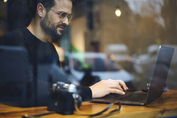 Bearded entrepreneur male in glasses dressed in black sweater reading news checking email and chatting with friends in social network using wireless internet connection at wooden table in coffee shop
