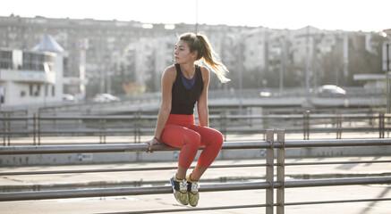Beautiful Caucasian woman athlete sitting outdoors.