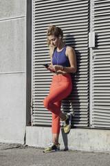 Portrait of beautiful sportswoman holding cell phone.
