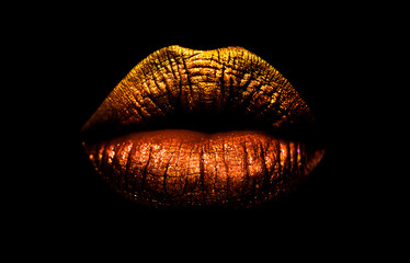 Golden brown lipstick on lips isolated on black background. Sexy lips, female mouth. Imprint lips. Luxury cosmetics for girls and women. Beautiful female lips. Female beauty concept girl