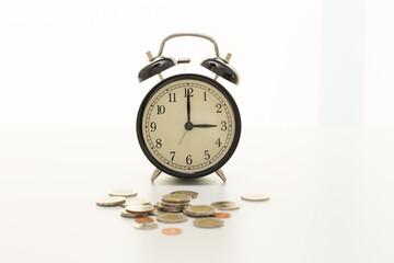 Vintage clock at three o'clock and coins
