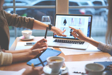 Cropped image of women hands pointing and choosing trendy look on internet websites for creating online presentation of fashionable clothes using digital computer sitting at table with cups of coffee