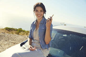 Smiling young woman holding car keys at a car