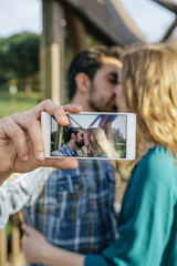 Kissing young couple taking selfie with smartphone