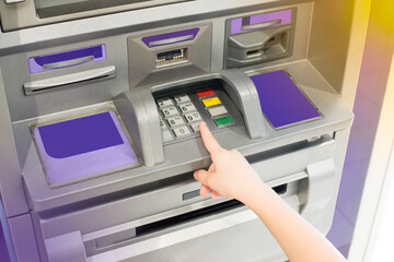 Hand of kid using ATM