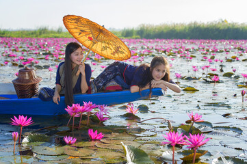 Laos women sleeping on the boat in flower lotus lake, Woman wearing traditional Thai people , Red Lotus Sea UdonThani Thailand