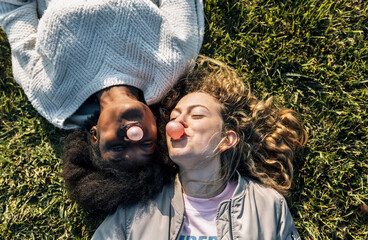 Two best friends making a gum bubble lying in the grass
