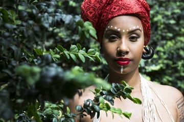 Portrait of young woman with piercings wearing traditional Brazilian headgear