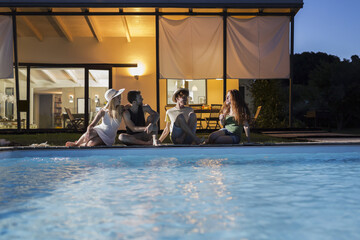 Four friends relaxing at the poolside at evening twilight