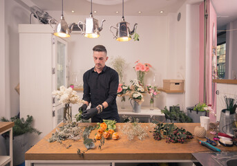 one man florist, arranging flowers, flower shop indoors