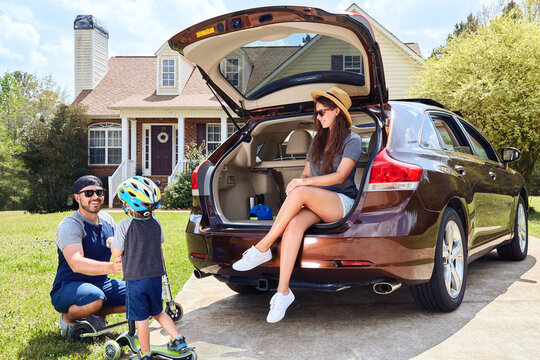 Family sitting in cars trunk near house. Mother, father, son.